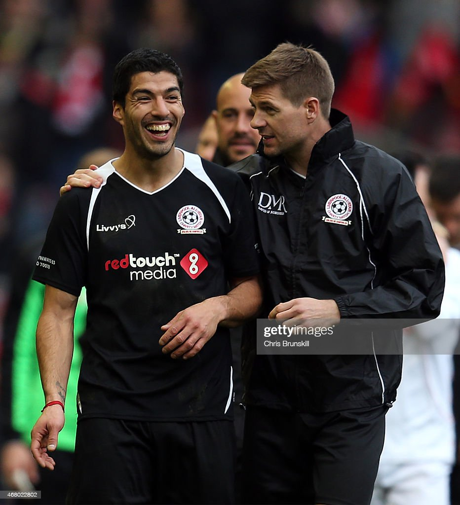 Luis Suarez and <a gi-track='captionPersonalityLinkClicked' href=/galleries/search?phrase=Steven+Gerrard&family=editorial&specificpeople=202052 ng-click='$event.stopPropagation()'>Steven Gerrard</a> of the Gerrard XI share a laugh at full time following the Liverpool All-Star Charity match at Anfield on March 29, 2015 in Liverpool, England.