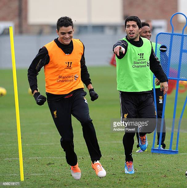 Luis Suarez and Tiago Ilori of Liverpool in action during a training session at Melwood Training Ground on December 13 2013 in Liverpool England
