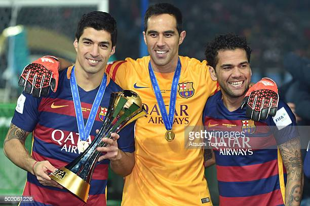 Luis Suarez Claudio Bravo and Dani Alves of FC Barcelona celebrate with the trophy during the final match between River Plate and FC Barcelona at...