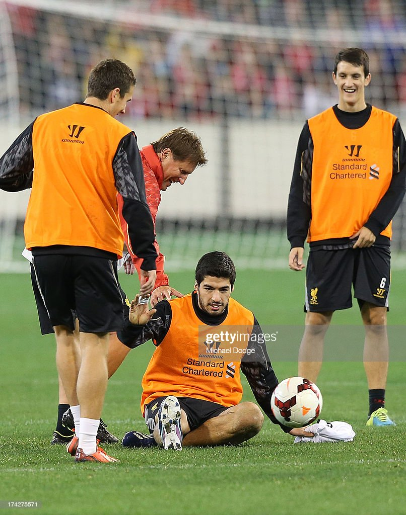 Luis Suarez is helped up after slipping over during a Liverpool FC training session at Melbourne Cricket Ground on July 23, 2013 in Melbourne, Australia.