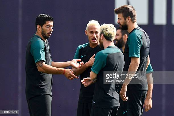 Luis Suarez Lionel Messi Neymar Jr and Gerard Pique of FC Barcelona share a joke during a training session ahead of their UEFA Champions League Group...