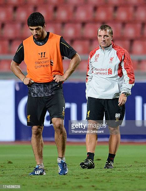 Luis Suarez looks on as manager Brendan Rodgers oversees a Liverpool FC training session at Rajamangala Stadium on July 27 2013 in Bangkok Thailand