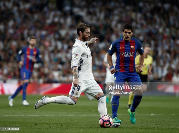 Luis Suarez of Barcelona and Sergio Ramos of Real Madrid vie for the ball during the La Liga match between Real Madrid and Barcelona at Santiago...