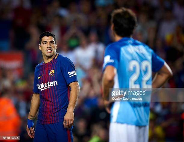 Luis Suarez of Barcelona argues with Paul Baysse of Malaga during the La Liga match between Barcelona and Malaga at Camp Nou on October 21 2017 in...
