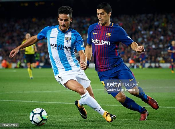 Luis Suarez of Barcelona competes for the ball with Juankar of Malaga during the La Liga match between Barcelona and Malaga at Camp Nou on October 21...