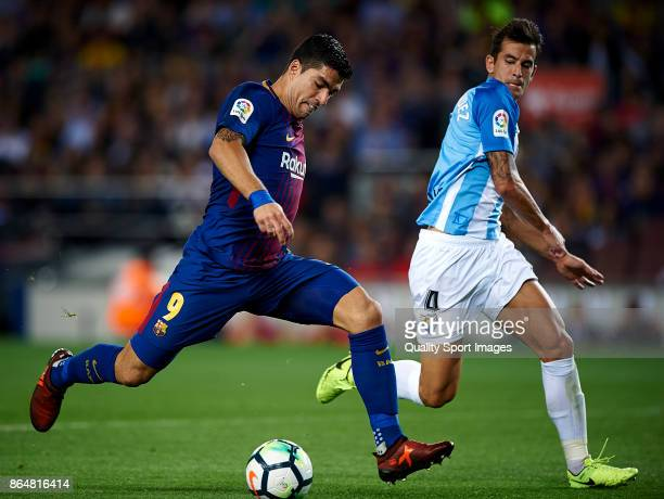 Luis Suarez of Barcelona competes for the ball with Luis Hernandez Rodriguez of Malaga during the La Liga match between Barcelona and Malaga at Camp...
