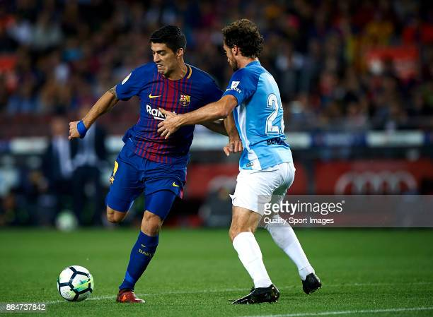 Luis Suarez of Barcelona competes for the ball with Paul Baysse of Malaga during the La Liga match between Barcelona and Malaga at Camp Nou on...