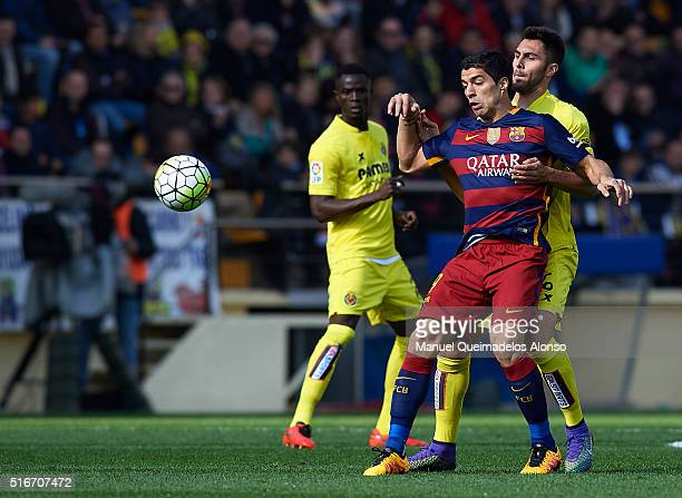 Luis Suarez of Barcelona competes for the ball with Victor Ruiz of Villarreal during the La Liga match between Villarreal CF and FC Barcelona at El...