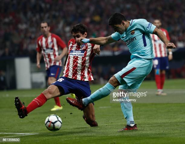 Luis Suarez of Barcelona in action against Stefan Savic of Atletico Madrid during the Spanish La Liga match between Atletico Madrid and Barcelona at...