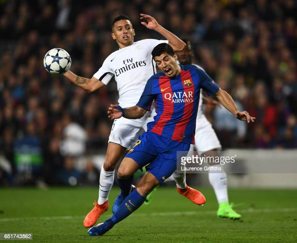 Luis Suarez of Barcelona is challenged by Marquinhos of PSG to earn a penalty during the UEFA Champions League Round of 16 second leg match between...