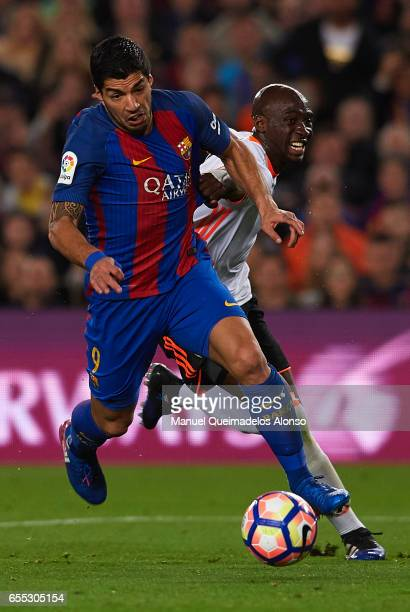 Luis Suarez of Barcelona is tackled by Eliaquim Mangala of Valencia during the La Liga match between FC Barcelona and Valencia CF at Camp Nou Stadium...
