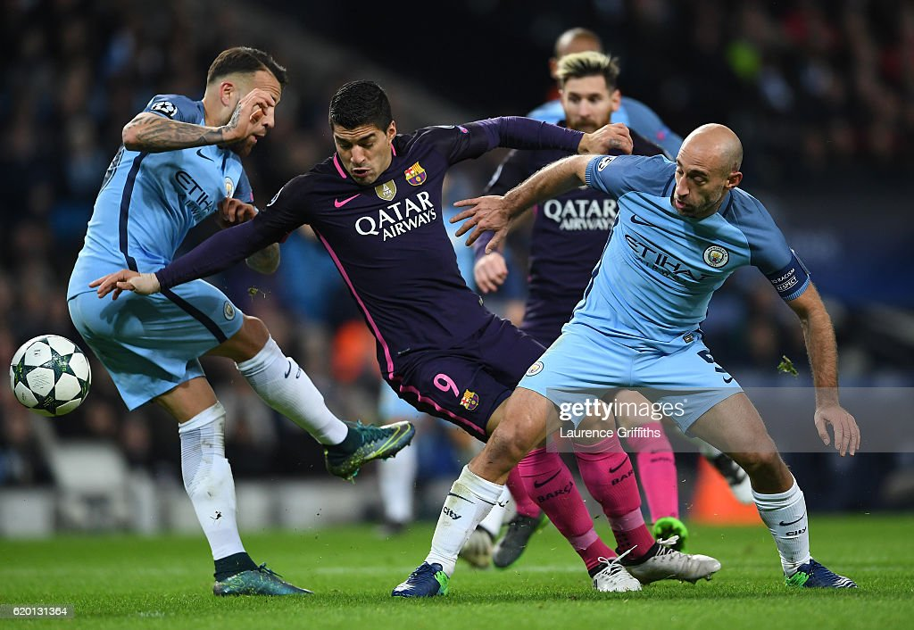 Luis Suarez of Barcelona (C) is tackled by Nicolas Otamendi of Manchester City (L) and Pablo Zabaleta of Manchester City (R) during the UEFA Champions League Group C match between Manchester City FC and FC Barcelona at Etihad Stadium on November 1, 2016 in Manchester, England.