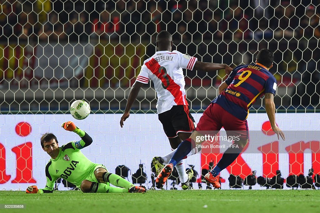 Luis Suarez of Barcelona scores his team's second goal despite the challenge from Eder Balanta of River Plate during the FIFA Club World Cup Final between River Plate and FC Barcelona at the International Stadium Yokohama on December 20, 2015 in Yokohama, Japan.