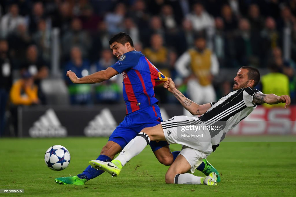 Luis Suarez of Barcelona shoots at goal under pressure from Leonardo Bonucci of Juventus during the UEFA Champions League Quarter Final first leg match between Juventus and FC Barcelona at Juventus Stadium on April 11, 2017 in Turin, Italy.
