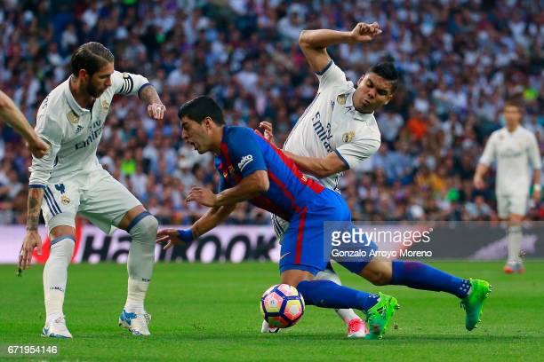 Luis Suarez of Barcelona takes on Casemiro and Sergio Ramos of Real Madrid during the La Liga match between Real Madrid CF and FC Barcelona at...