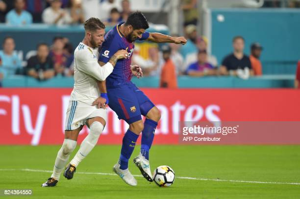 Luis Suarez of Barcelona vies for the ball with Sergio Ramos of Real Madrid during their International Champions Cup football match at Hard Rock...