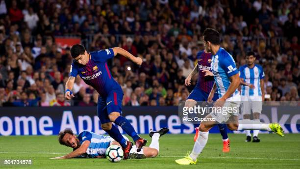 Luis Suarez of FC Barcelona advances with the ball between Paul Baysse and Luis Hernandez of Malaga CF during the La Liga match between Barcelona and...