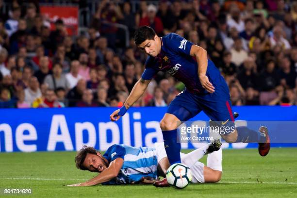 Luis Suarez of FC Barcelona advances with the ball under pressure from Paul Baysse of Malaga CF during the La Liga match between Barcelona and Malaga...
