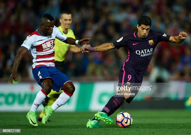 Luis Suarez of FC Barcelona being followed by Uche Wakaso Mubarak of Granada CF during the La Liga match between Granada CF v FC Barcelona at Estadio...