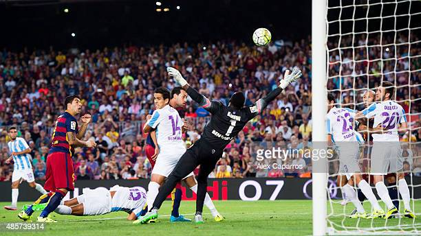 Luis Suarez of FC Barcelona broughts down Marcos Angeleri of Malaga CF and head the ball towards goal during the La Liga match between FC Barcelona...