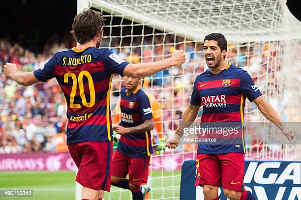 Luis Suarez of FC Barcelona celebrates with his teammate Sergi Roberto after scoring the opening goal during the La Liga match between FC Barcelona...