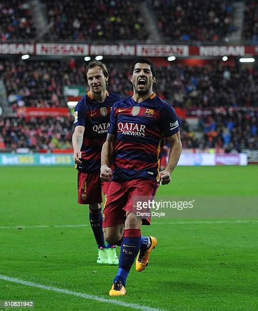Luis Suarez of FC Barcelona celebrates with Ivan Rakitic after scoring his team's 3rd goal during the La Liga match between Sporting Gijon and FC...