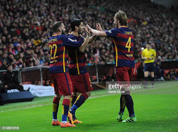 Luis Suarez of FC Barcelona celebrates with Ivan Rakitic and Aleix Vidal after scoring his team's 3rd goal during the La Liga match between Sporting...