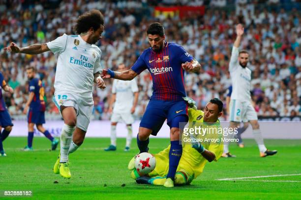 Luis Suarez of FC Barcelona clashes with goalkeeper Keylor Navas of Real Madrid CF as his teammate Marcelo follows them during the Supercopa de...