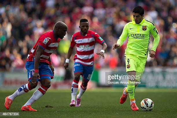 Luis Suarez of FC Barcelona competes for the ball JeanSylvain Babin of Granada CF during the La Liga match between Granada CF and FC Barcelona at...
