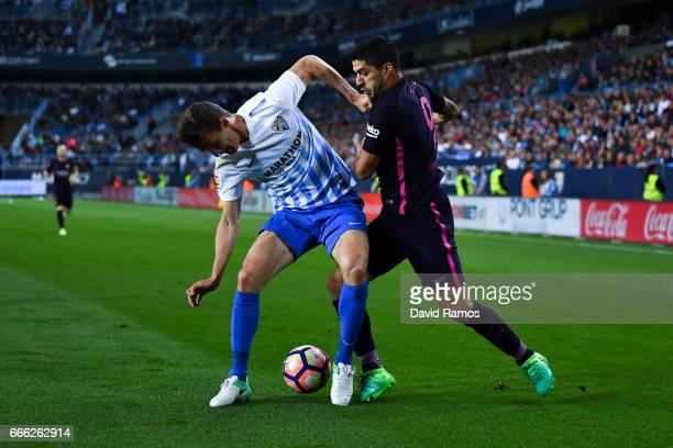 Luis Suarez of FC Barcelona competes for the ball with Diego Llorente of Malaga CF during the La Liga match between Malaga CF and FC Barcelona at La...
