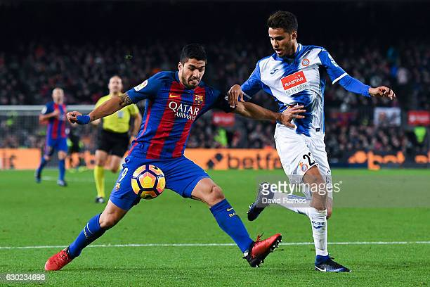 Luis Suarez of FC Barcelona competes for the ball with Diego Reyes of RCD Espanyol during the La Liga match between FC Barcelona and RCD Espanyol at...