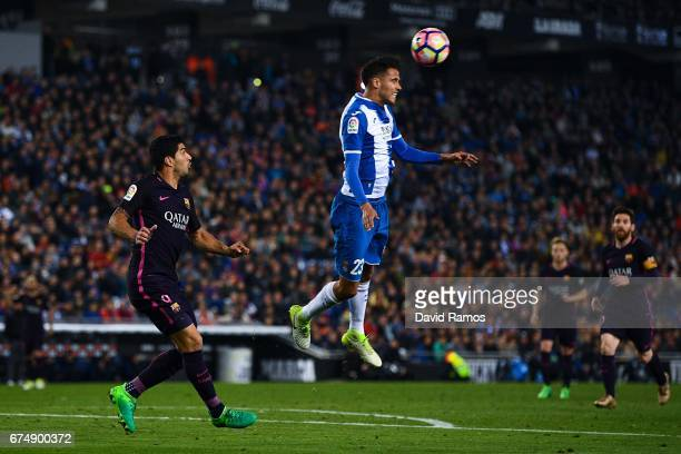 Luis Suarez of FC Barcelona competes for the ball with Diego Reyes of RCD Espanyol during the La Liga match between RCD Espanyol and FC Barcelona at...