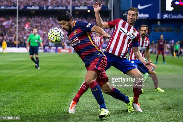 Luis Suarez of FC Barcelona competes for the ball with Gabi Fernandez of Atletico de Madrid during the La Liga match between Club Atletico de Madrid...