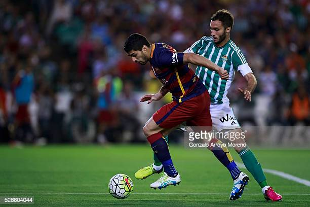 Luis Suarez of FC Barcelona competes for the ball with German Pezzella of Real Betis Balompie during the La Liga match between Real Betis Balompie...