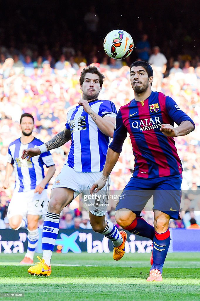 Luis Suarez of FC Barcelona competes for the ball with Inigo Martinez of Real Sociedad de Futbol during the La Liga match between FC Barcelona and...