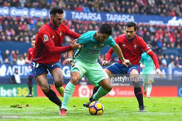 Luis Suarez of FC Barcelona competes for the ball with Ivan Marquez and Miguel Flanonof CA Osasuna during the La Liga match between CA Osasuna and FC...