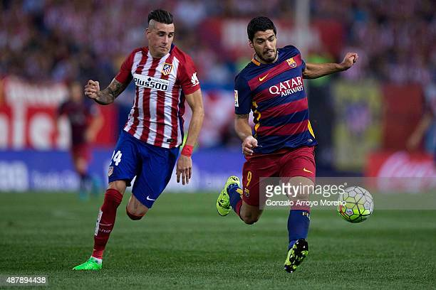 Luis Suarez of FC Barcelona competes for the ball with Jose Maria Gimenez of Atletico de Madrid during the La Liga match between Club Atletico de...