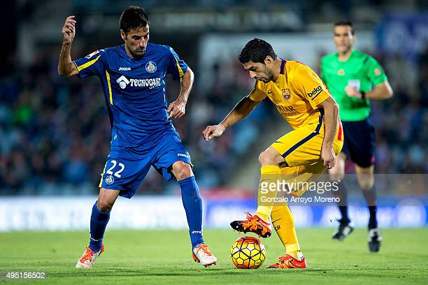 Luis Suarez of FC Barcelona competes for the ball with Juan Antonio Rodrguez of Getafe CF during the La Liga match between Getafe CF and FC Barcelona...
