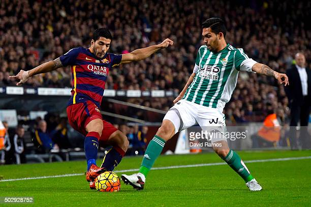 Luis Suarez of FC Barcelona competes for the ball with Juan Vargas of Real Betis Balompie during the La Liga match between FC Barcelona and Real...