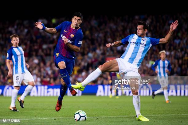 Luis Suarez of FC Barcelona competes for the ball with Luis Hernandez of Malaga CF during the La Liga match between Barcelona and Malaga at Camp Nou...