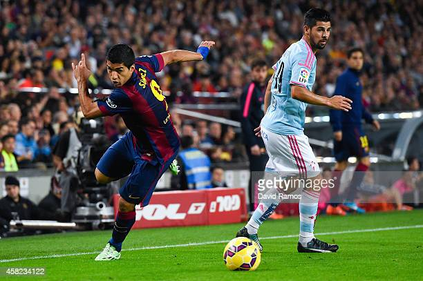 Luis Suarez of FC Barcelona competes for the ball with Nolito of Celta de Vigo during the La Liga match between FC Barcelona and Celta de Vigo at...