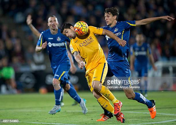 Luis Suarez of FC Barcelona competes for the ball with Santiago Vergini of Getafe CF and his teammate Damian Suarez during the La Liga match between...