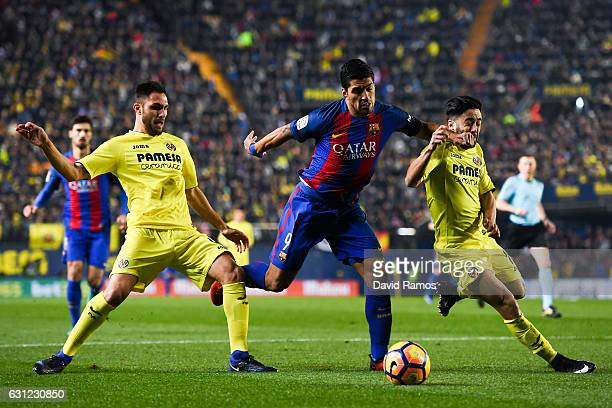 Luis Suarez of FC Barcelona competes for the ball with Victor Ruiz and Jaume Costa of Villarreal CF during the La Liga match between Villarreal CF...