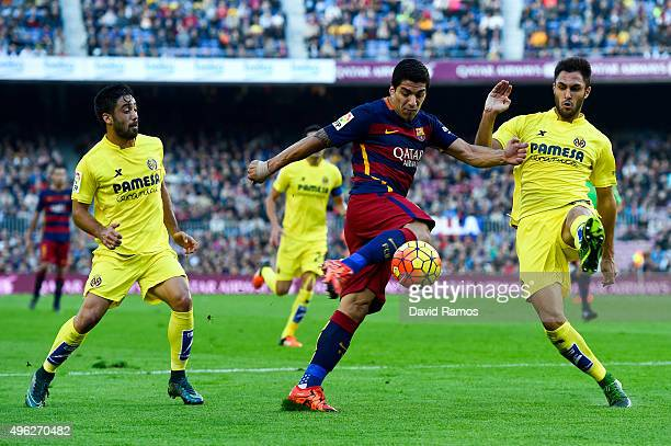 Luis Suarez of FC Barcelona competes for the ball with Villarreal CF players during the La Liga match between FC Barcelona and Villarreal CF at Camp...