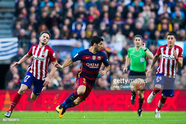 Luis Suarez of FC Barcelona conducts the ball between Saul Niguez and Jose Maria Gimenez of Club Atletico de Madrid during the La Liga match between...
