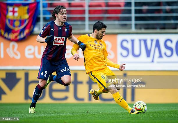 Luis Suarez of FC Barcelona duels for the ball with Aleksandar Pantic of SD Eibar during the La Liga match between SD Eibar and FC Barcelona at...