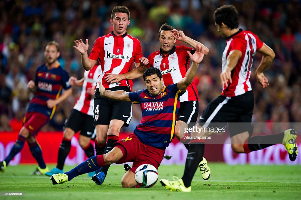 Luis Suarez of FC Barcelona falls between Aymeric Laporte Carlos Gurpegi and Xabier Etxeita of Athletic Club during the Spanish Super Cup second leg...
