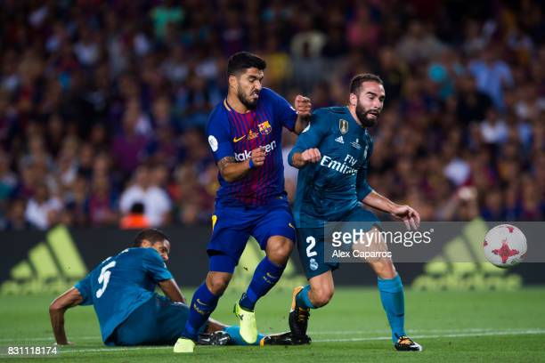 Luis Suarez of FC Barcelona fights for the ball between Raphael Varane and Daniel Carvajal of Real Madrid CF during the Supercopa de Espana Supercopa...