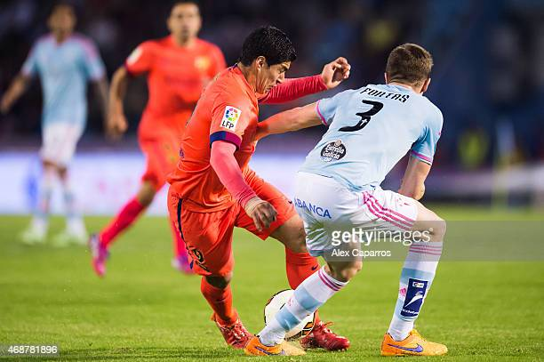 Luis Suarez of FC Barcelona fights for the ball with Andreu Fontas of Celta Vigo during the La Liga match between Celta Vigo and FC Barcelona at...