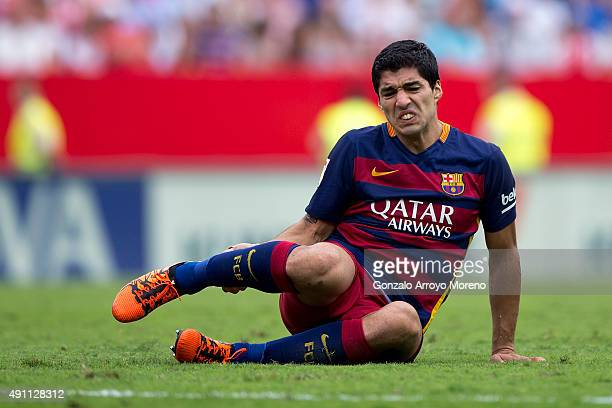 Luis Suarez of FC Barcelona grimmaces in pain after being tackled during the La Liga match between Sevilla FC and FC Barcelona at Estadio Ramon...
